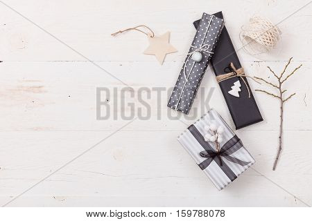Top view on hands packing nice Christmas gifts. Presents decor elements on wooden background. Holidays and winter concept.
