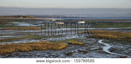 Boats In Low Tide Mudflats Of Empty Harbour At Sunrise