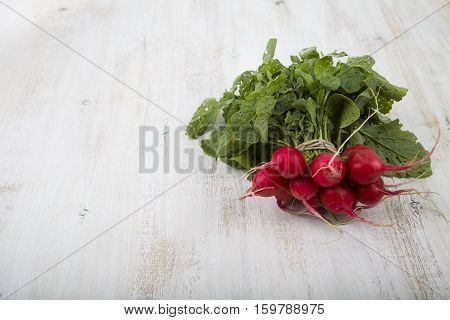 Ripe Red Radish With Leaves On A Wooden Table Close-up. Fresh Vegetables. Healthy Eating.