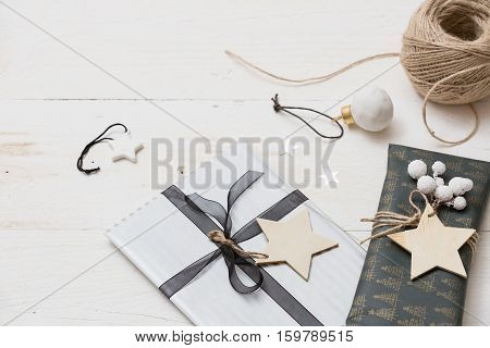 Nice Christmas gifts packed in black and striped paper and decorated with stars on wooden background. Presents and decor elements. Holidays and winter concept.