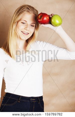 young pretty blond woman choosing between red and green apple smiling slim, lifestyle diet concept