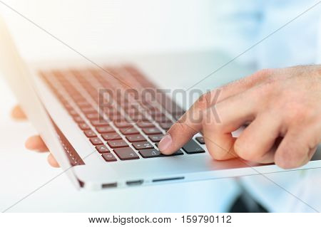 Image of a finger being about to press a key on a laptop keyboard