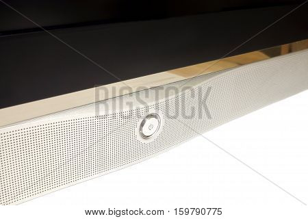 Power on button on modern TV receiver with blank black screen and silver panel with many small holes side view isolated on white