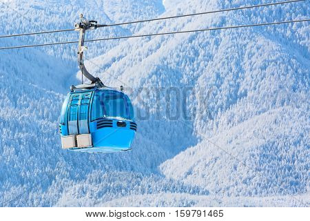 Blue cable car cabin ski lift and snow mountain pine trees at the background