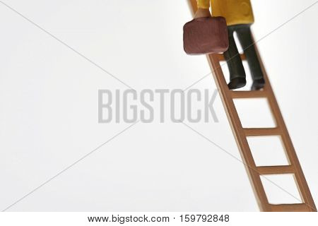 Businessman figurine climbing ladder, low section