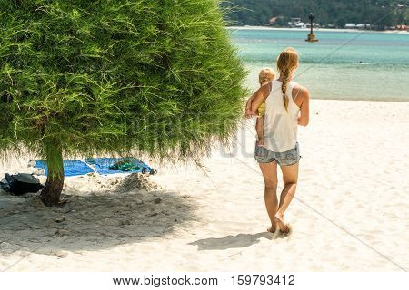 Young Woman With A Child Go To The Sea