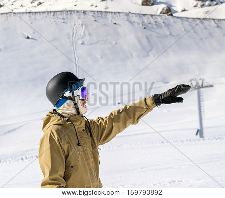 Portrait of young snowboarder in helmet and sunglass mask at the ski resort Elbrus on background of mountains and indicates hand into the distance