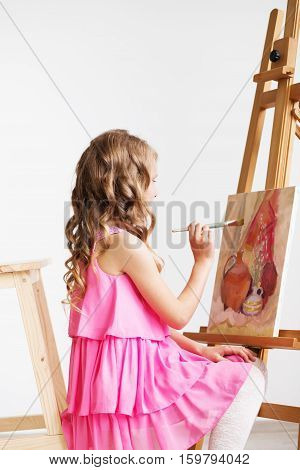 Portrait Of A Lovely Little Girl Painting A Picture In A Studio Or Art School.