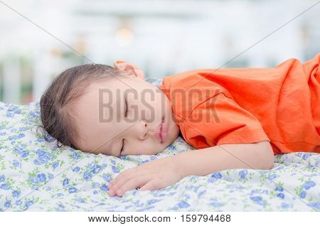 Little Asian girl sleeping on bed at day time