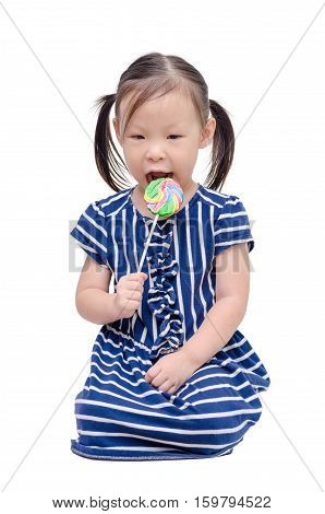 Little asian girl eating lollipop over white