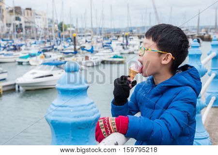 Young asian boy eating ice cream at harbor