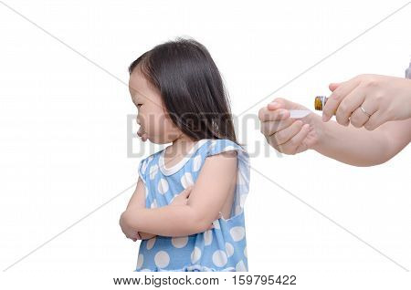 Displeased girl refuse to have medicine from her mother
