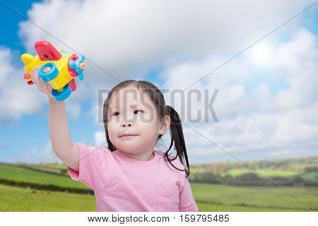 Little asian girl playing with plastic plane in grass field