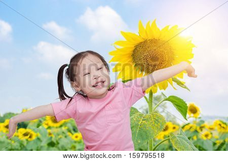 Happy little asian girl at sunflower field in the morning