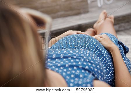 Cropped Outdoor Shot Of Young Pregnant Female Wearing Dress Sunbathing On Sunlounger During Vacation