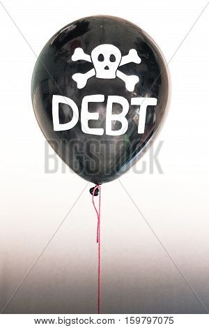 The word debt in white and a skull and cross bones on a balloon illustrating the concept of a debt bubble, debt default, mortgage stress, student loans, auto loans, US, EU and other sovereign country  debt.