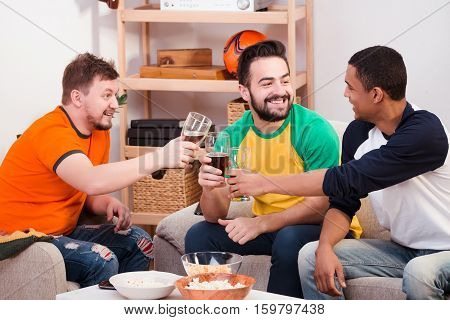 Happy friends drinking beer at home. Hnadsome men communicating and spending their weekends all together.