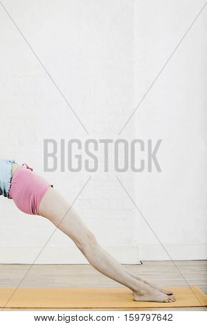 Low section of woman doing back bend on yoga mat at gym