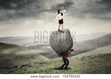 Young businesswoman standing on the stone and shouting with a megaphone while her partner carrying the stone on the hill