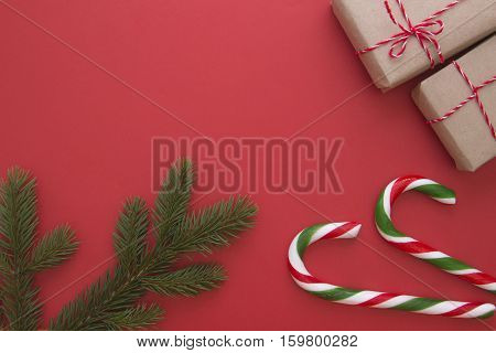 Christmas background with fir twings, Xmas gifts and candy canes. Top view, flat lay. Copy space for text. Winter holidays concept