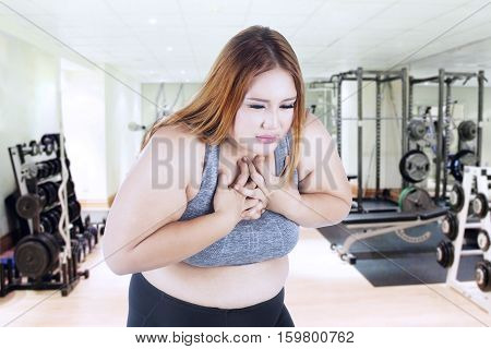 Portrait of fat woman getting heart attack while standing in fitness center