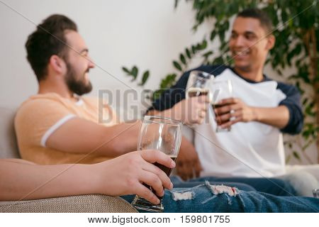 Picture of happy friends drinking beer at home. Handsome men spending free time or weekedns all together after hard working day or week.