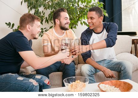 Picture of happy friends drinking alcohol drinks at home all together. Handsome men drinking beers and eating pop corn.