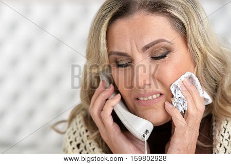 Portrait of sick mature woman talking on the phone