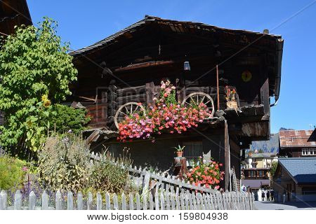 Wooden houses wreathed with flowers in a mountain village in the Alps.
