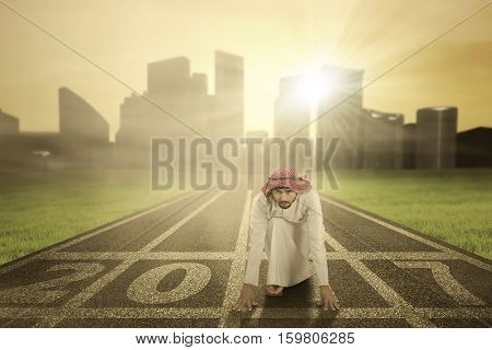 Image of young Arabian businessman kneels and ready to race with numbers 2017 on the asphalt track