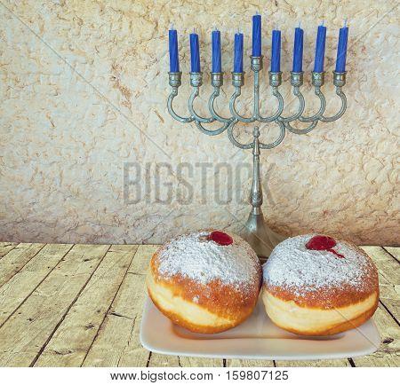 Jewish menorah and sweet donuts are traditional symbols for Hanukkah holiday