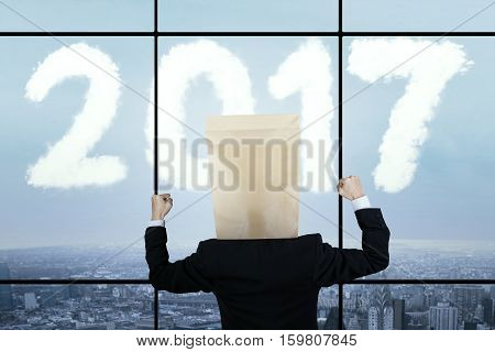 Image of businessman wearing cardboard on his head while celebrating his success with clouds shaped numbers 2017