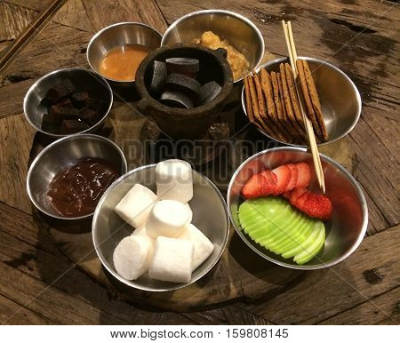 Party chocolate and caramel fondue with mamellow brownie biscuit strawberry and apple on the wood table