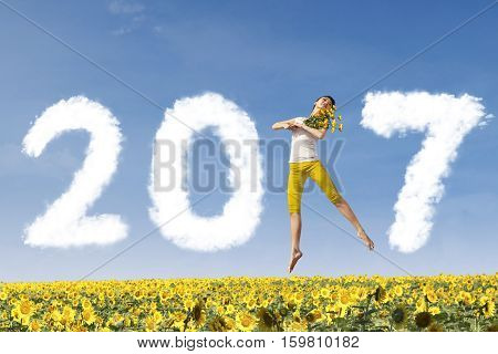 Picture of an attractive woman is holding flowers and jumping in the sunflower garden while forming numbers 2017