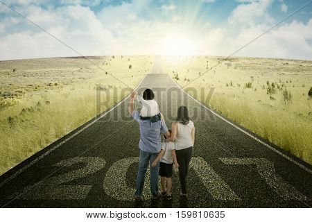 Back view of happy family looking at the sunrise while walking on the asphalt road with numbers 2017