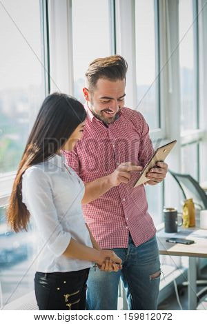 Handsome businessman showing his collegue new diagram or scheme represented on tablet PC while working in office interior. Business concept.