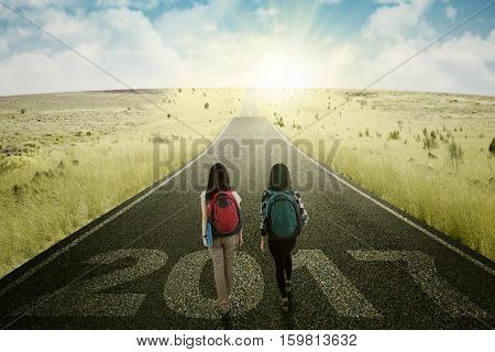 Image two female students while walking on the road with numbers 2017 and bright sunlight
