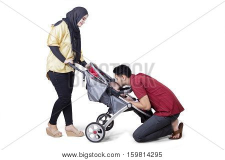 Portrait of young parents strolling and kissing their baby in the stroller isolated on the background