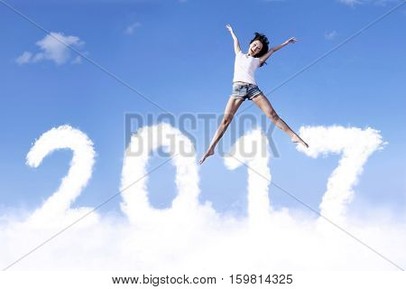 Image of young woman leaping above clouds shaped numbers 2017 on the blue sky