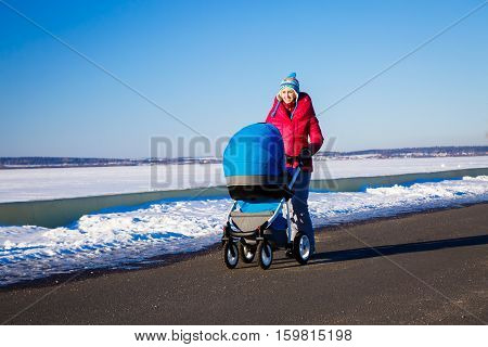 Happy Mother with Baby Stroller Walking in Winter Park and Enjoying Sunny Day. Snowy Background. Happy Parenting and Healthy Lifestyle Concept. Photo with Copy Space.