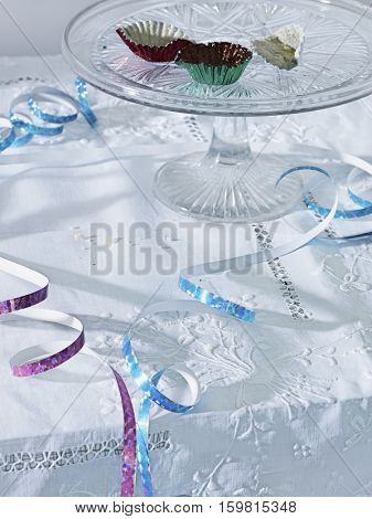 Cup cake wraps amongst streamers on table, elevated view
