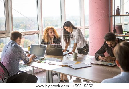 Communication between two business colleagues ladies while working in board room in office. Red haired lady explaining her worker what to start with. Business concept.