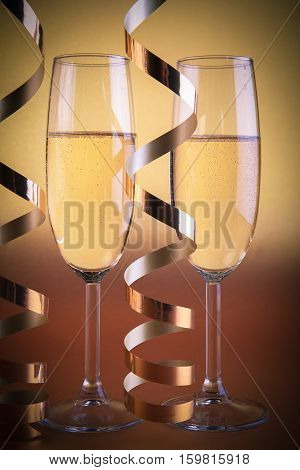 Two champagne glasses, and decoration on golden background