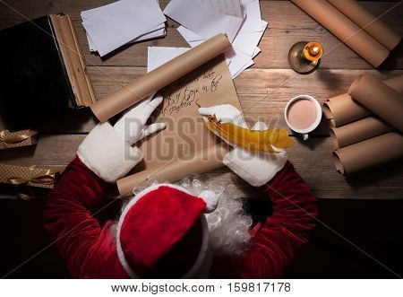 Santa Claus sitting at his room and writing Christmas letter or wish list