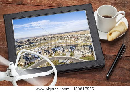 real estate aerial photography concept - reviewing  pictures of of new house development on a tablet with a drone and coffee, screen image copyright by the photographer
