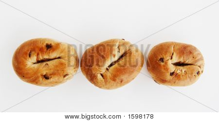 Three raisin bagels on a white