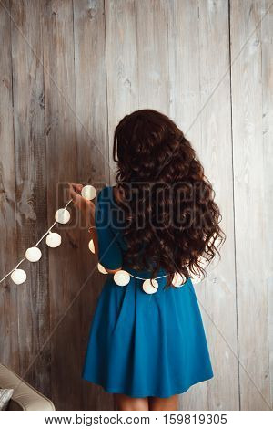 Beautiful Young Girl In A Blue Dress And Long Hair With A Christmas Garland From The Back