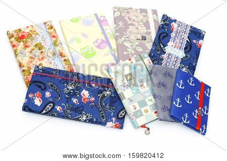 Collection of eight handmade scrapbooking holders for travel documents with ribbon closure. Different fabric design. isolated on white background.