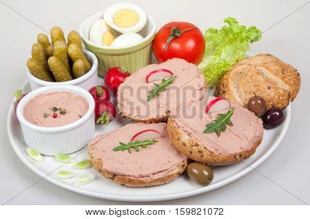 plate with slices of bread with home made pate decorated with vegetables