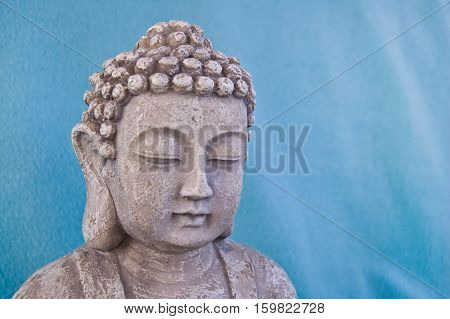 Buddha face on blue background. Symbol of Buddhism religion